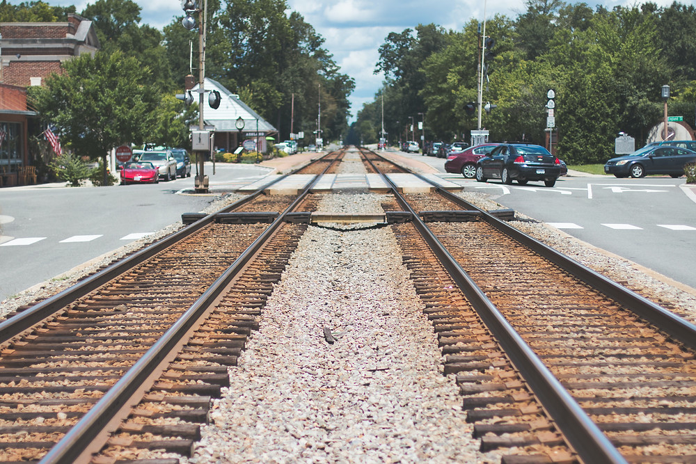 This image shows a set of empty railroad tracks with vehicles at an intersection to the right.