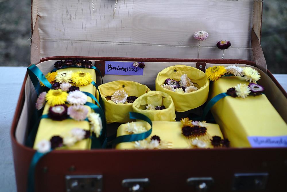 Barrettes, peignes et boutonnières en fleurs séchées, présentés dans une valise ancienne