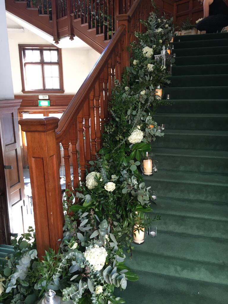 statement floral staircase arrangement white hydrangeas and eucalyptus