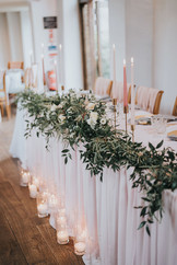 greenery and floral top tale with tall pink dinner candles and drapery