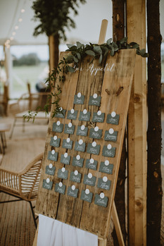 escort cards table plan with dusky blue colours and greenery to decorate - rustic