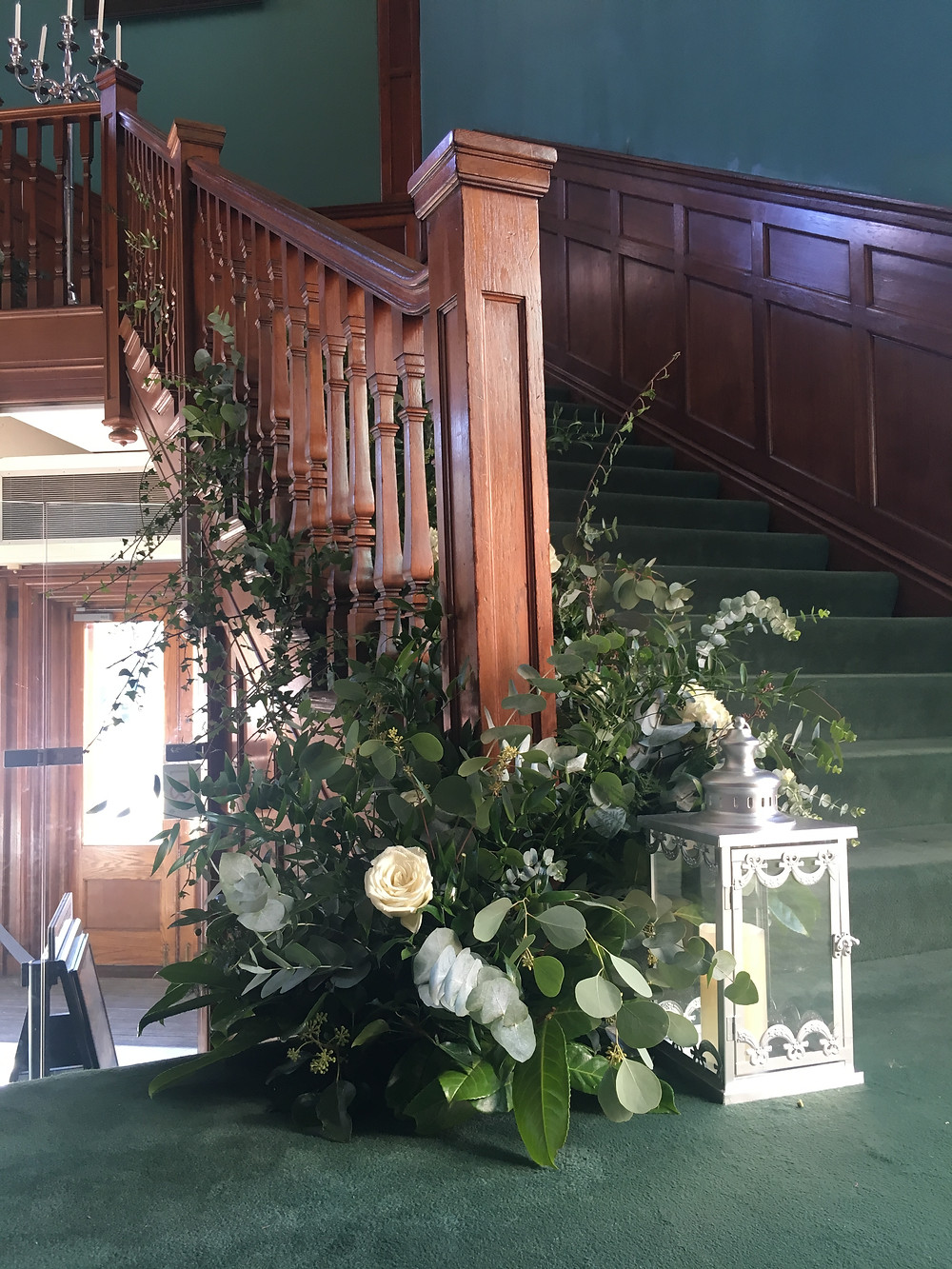 statement floral staircase arrangement white roses and foliage