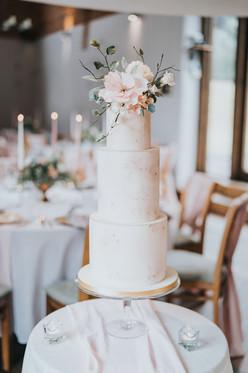 three teir wedding cake with blush pink icing and fondant flowers