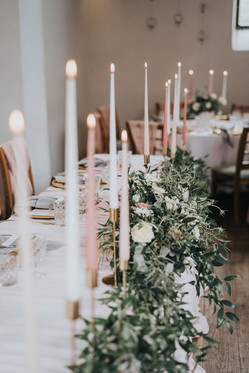 tall ester and erik wedding day candles with greenery