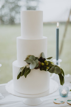 simple white wedding cake with three teirs and greenery on white cake stand