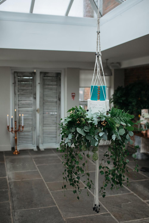 hanging macrame cake holder with trailing folaige base