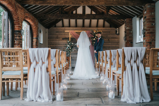 lattice grey wedding ceremony chairs with candles down the aisle