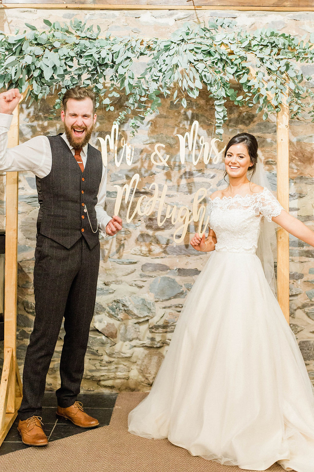 wedding photo booth backdrop with greenery and signage
