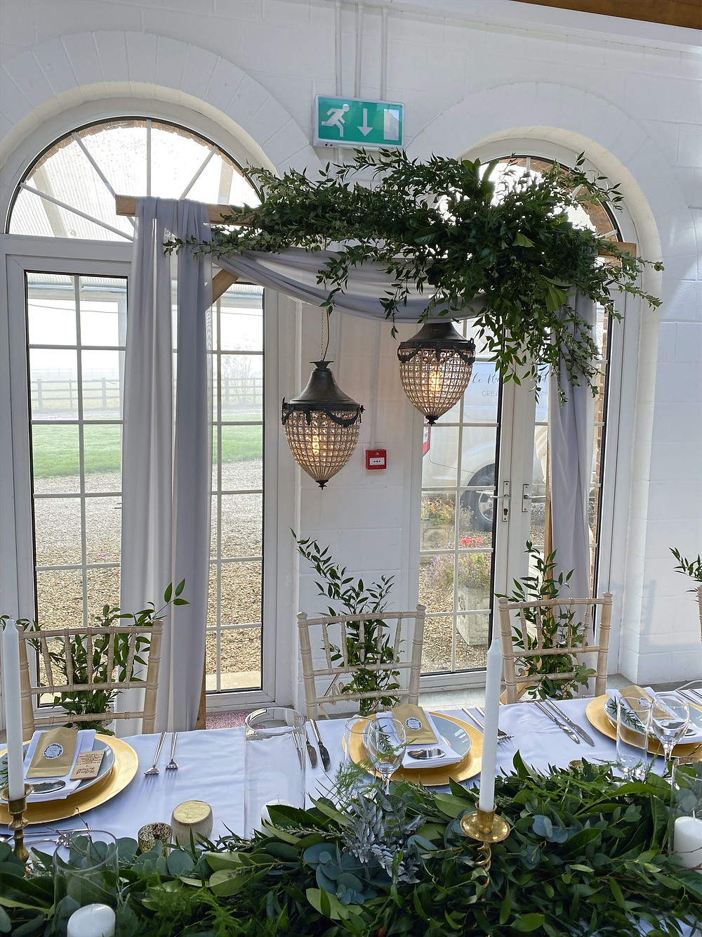 archway backdrop with vintage lights and greenery