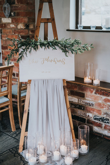 calligarphy draped wedding welcome sign  with candles at the base