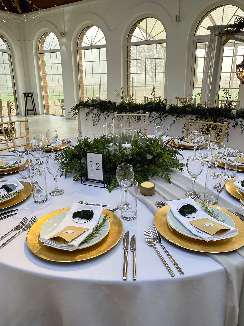 low greenery centrepiece with gold charger plates