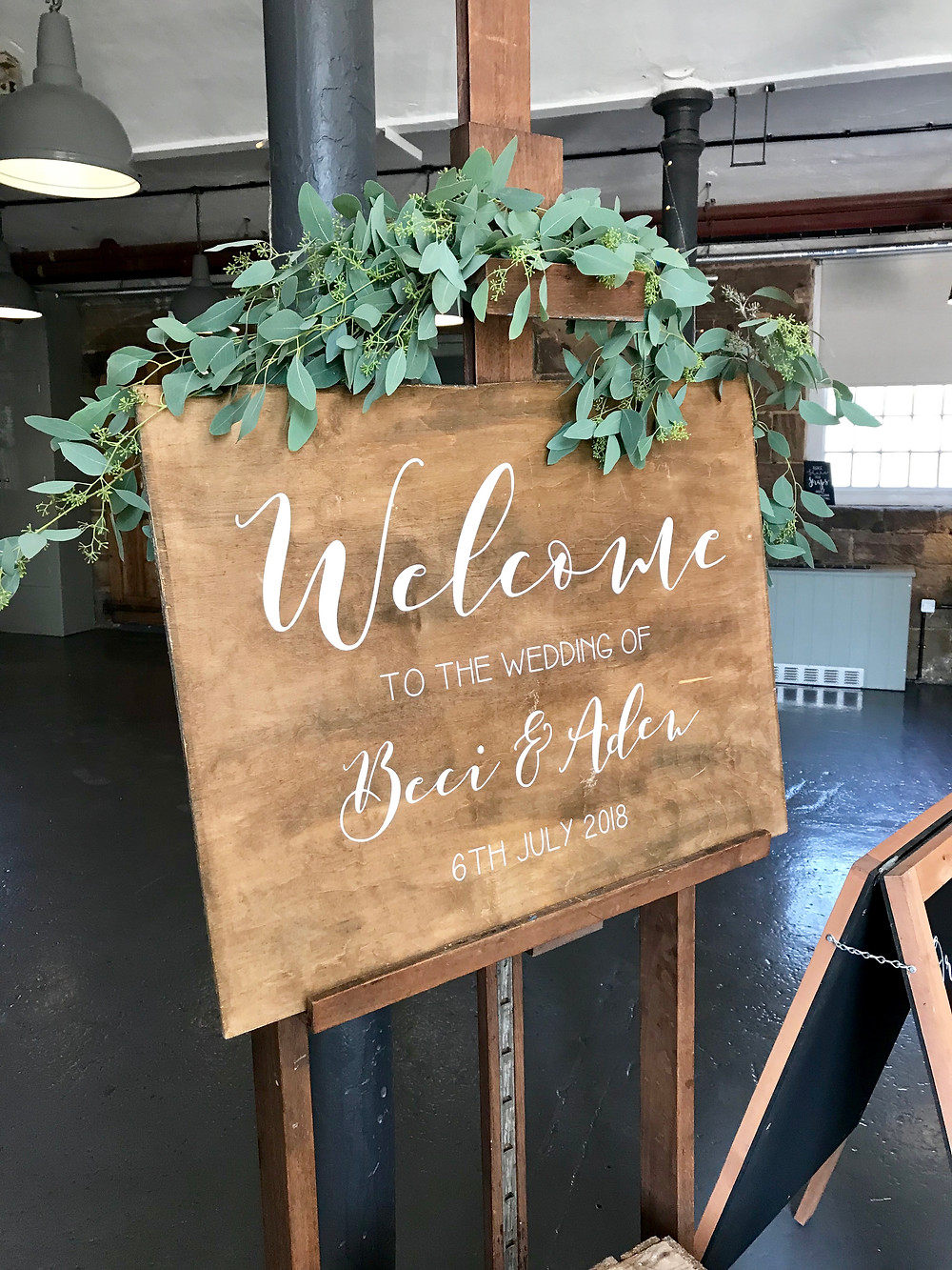 wooden rustic welcome sign for wedding at the west mill venue