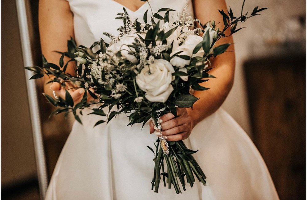 bridal bouquet with white flowers and dark greens
