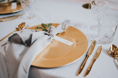 calligraphy place names with gold charger plate and grey napkin with greenery and gold cutlery