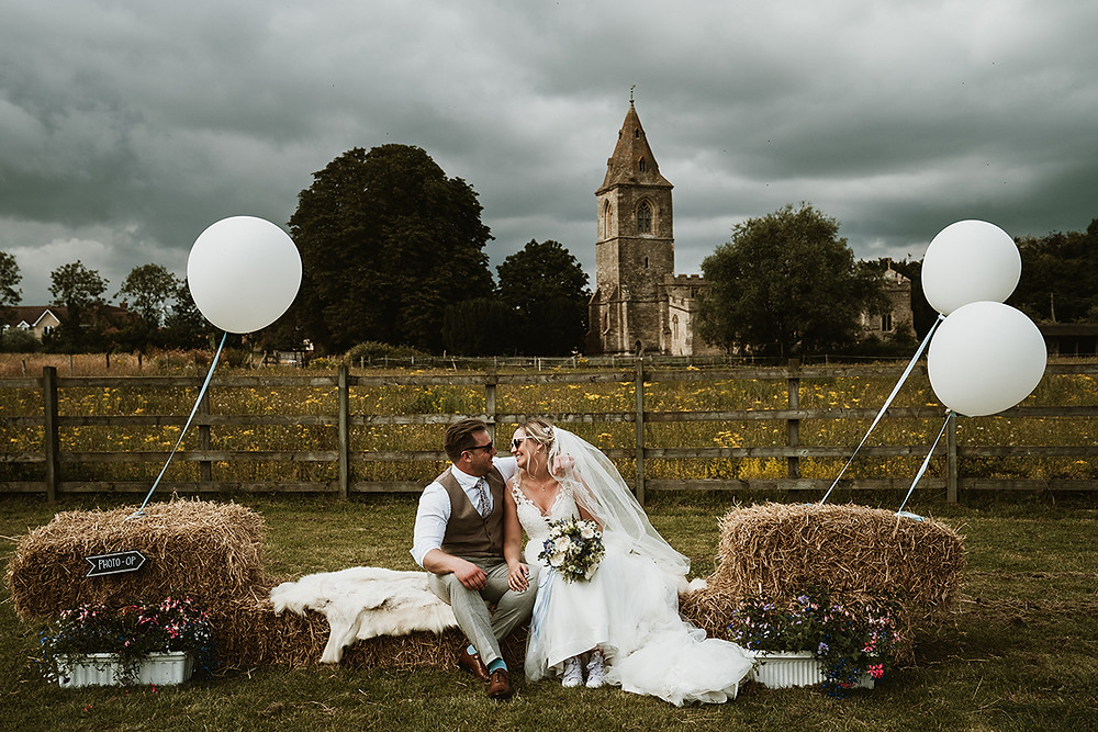 outdoor tipi wedding with straw bales and giant balloons