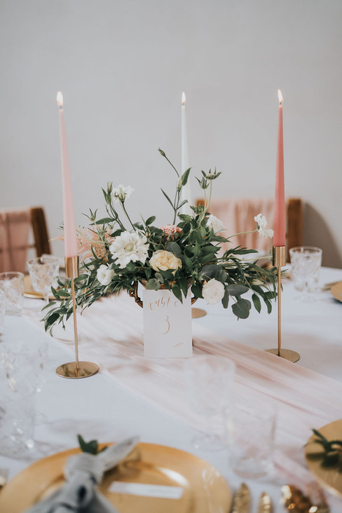 blush pink floral centre piece with candles and table number