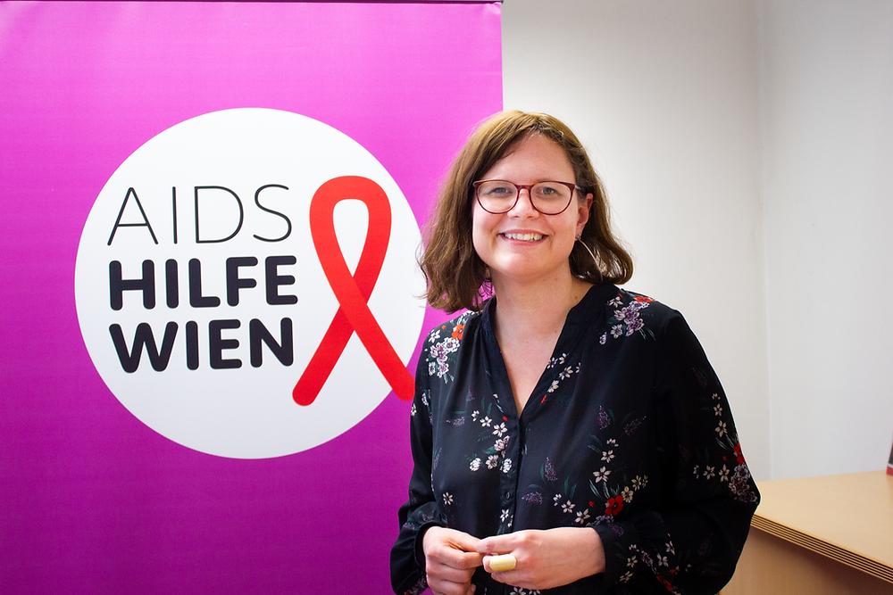 Geschäftsführerin Andrea Brunner steht neben einem Plakat der Aids Hilfe Wien mit lila Hintergrund und roter Schleife