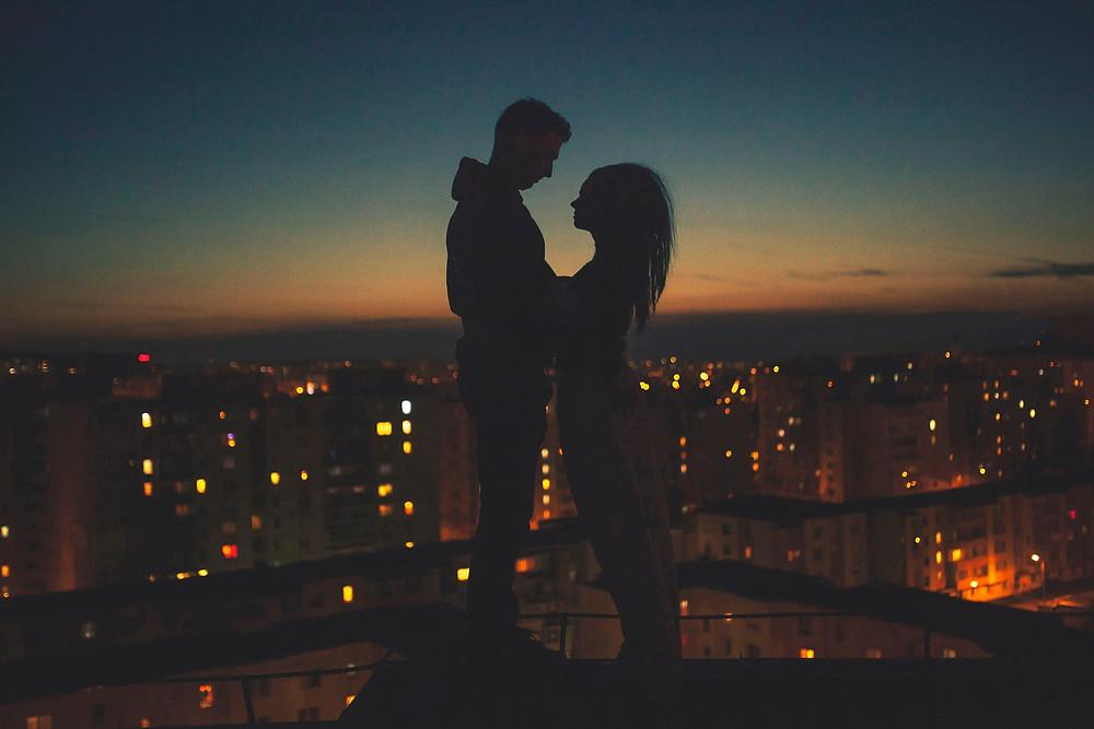Silhouetten zweier Menschen, die sich nachts näher kommen