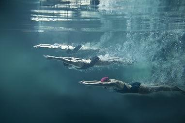 People swimming deep below the surface of the ocean.