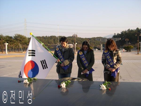 임씨와 두 선거운동원이 망월동 위령탑 앞에헌화하고 영령들을 위해 묵념하고 있다