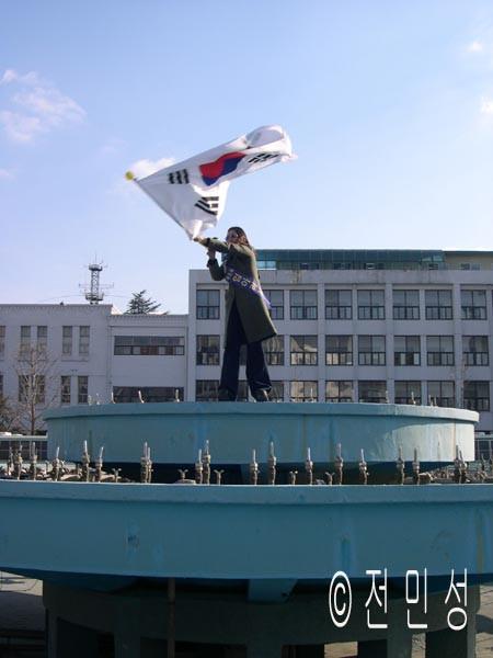 후보 임아리사 씨가 전남도청 앞 분수대에서 태극기를 휘날리고 있다.