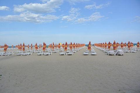 Strand mit Sonneliegen und Sonnenschirmen