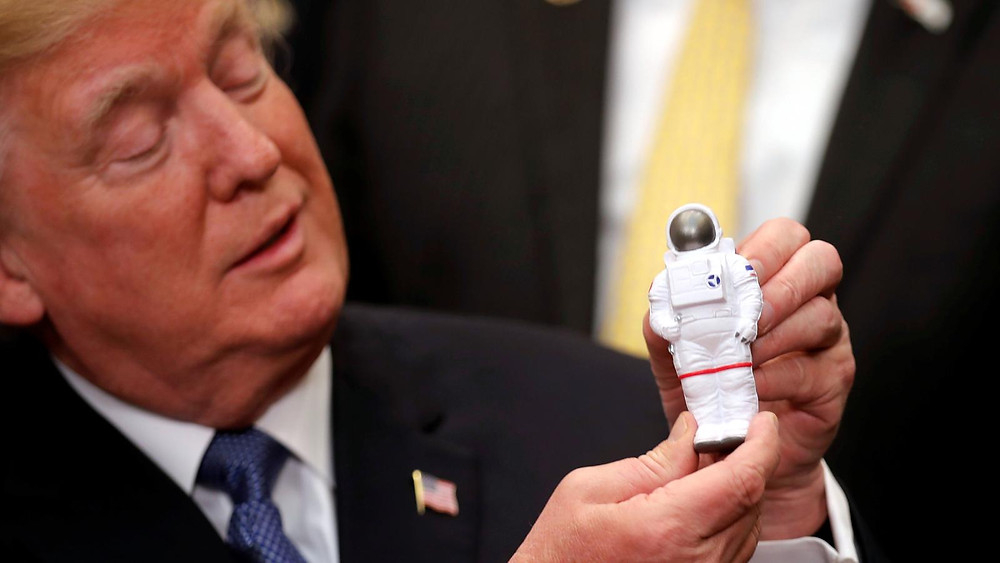 "The Great Big Cheeto ""Trump"" Holding an Astronaut Figurine During His Government Shutdown with NASA (Credit: Quartz)"