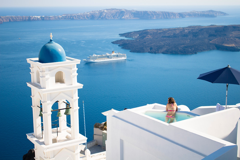 Woman in a private pool with spectacular view from Santorini, Greece.