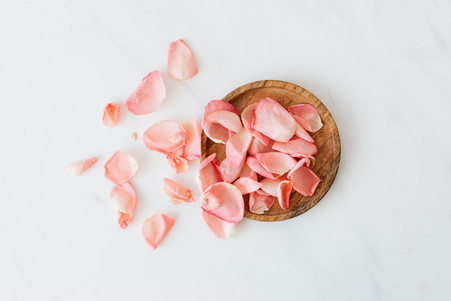 rose-petals-and-wooden-plate-on-white-ba