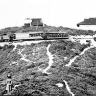 circa 1912 - A woman watches a train arrive at the Tavern. Seen (right to left) is the archway, dance pavilion and Federal Weather Station, where weather data was gathered and compared to data from San Francisco, in an attempt to understand weather and forecast it.