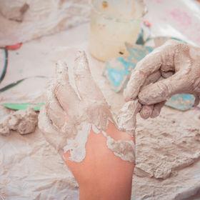 Closeup of children's dirty hands in cla