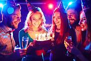 Young people around birthday cake.jpg