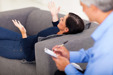 middle aged woman lying on sofa and talk