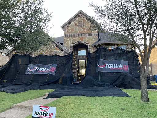 A house covered with black cloth and Hawk 3 Construction banners | Roofing Contractors Texas