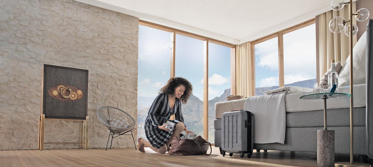 foto de uma mulher de vestido preto e branco com listras verticais, agachada mexendo em sua bolsa em seu quarto com tons neutros. Ela está com uma meia de compressão da Selecta demonstrando flexibilidade e qualidade.