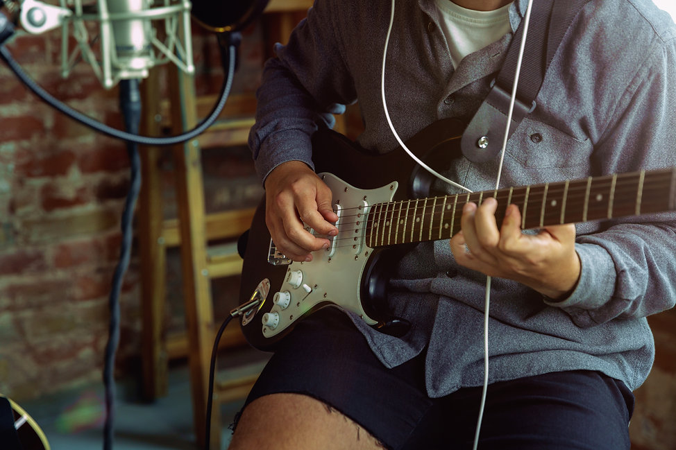 young-man-recording-music-playing-guitar