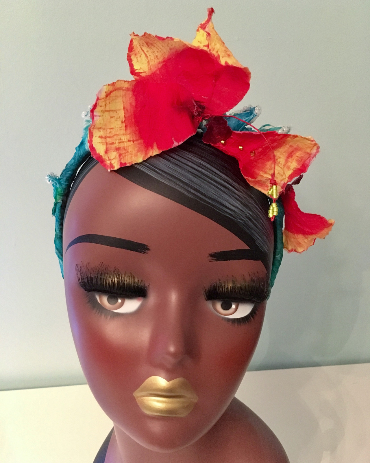 With a lively sense of motion, this headband features a hibiscus bloom  being carried away on a wave. The headband and flower are crafted with  hand-sculpted ...