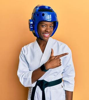 Young african american girl wearing taekwondo kimono and protection helmet smiling cheerfu