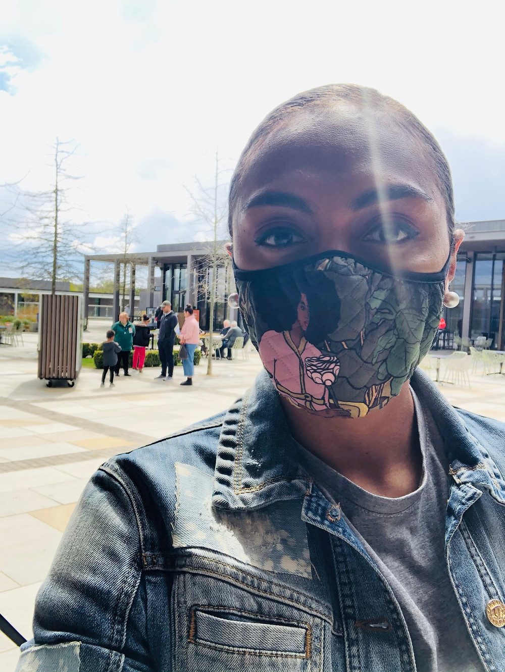 Isabella is facing the camera whilst wearing a mask with the image of a black woman holding flowers. She is wearing a grey t-shirt and a blue denim jacket.