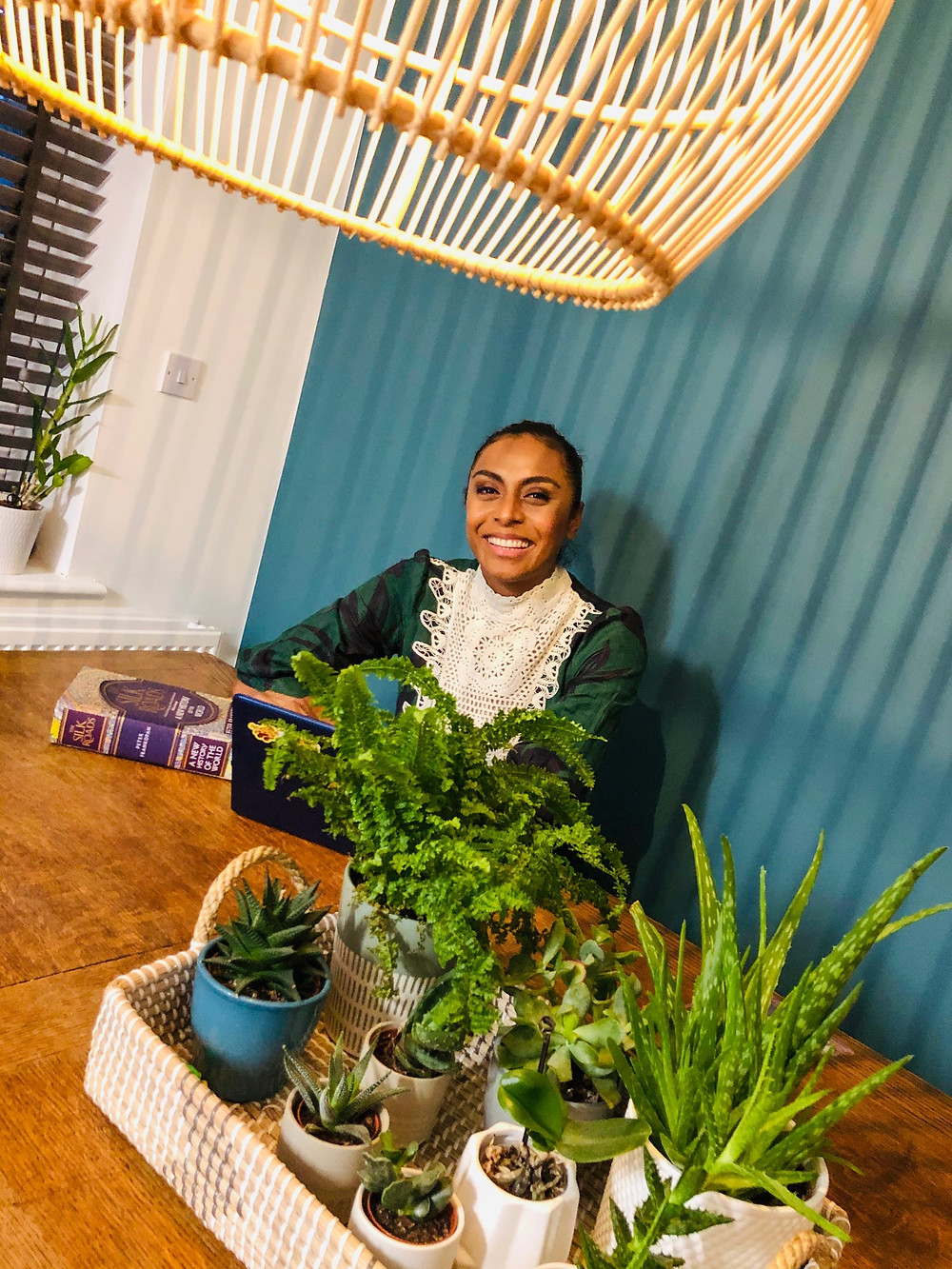 Isabella is sitting at the end of a wooden dining table which has a fibre basket of potted plants in the middle of it. She has a book with a purple cover on the table in front of her, and her laptop is partially seen behind one of the potted plants. She has on a green dress with a white embroidered collar. The feature wall behind her is topaz in colour and there is a window with grey blinds to her left. At the very top left corner of the picture is a partial image of a bamboo lampshade.