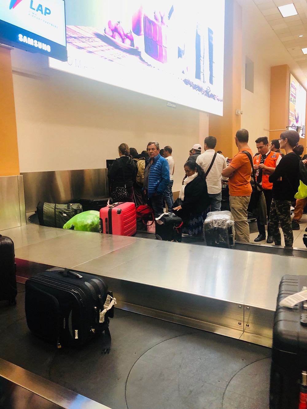 Fijian In The UK - Luggage carousel at airport, people impatiently pulling bags off from the beginning of the carousel and jamming the machine