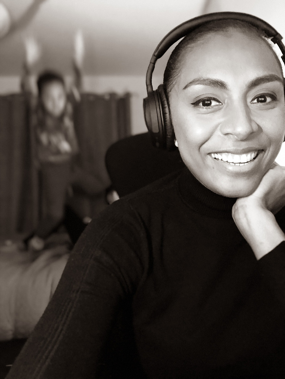 Isabella is at the forefront of the image and smiling into the camera, she is wearing a black turtleneck top and has her resting on the palm of her left hand. She also has black headphones over her head and on her ears. and the silhouette of her son is jumping in the air, in the background. The photogrpah is in black and white.