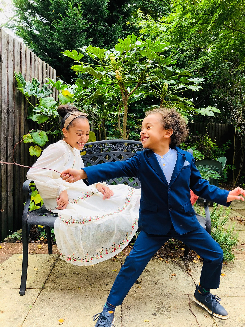 Girl wearing a white embroidered dress sitting on a black bench laughing while a boy in blue suit with blue dress shoes is standing in front of her with a stick. The boy is also laughing as he strikes a pose