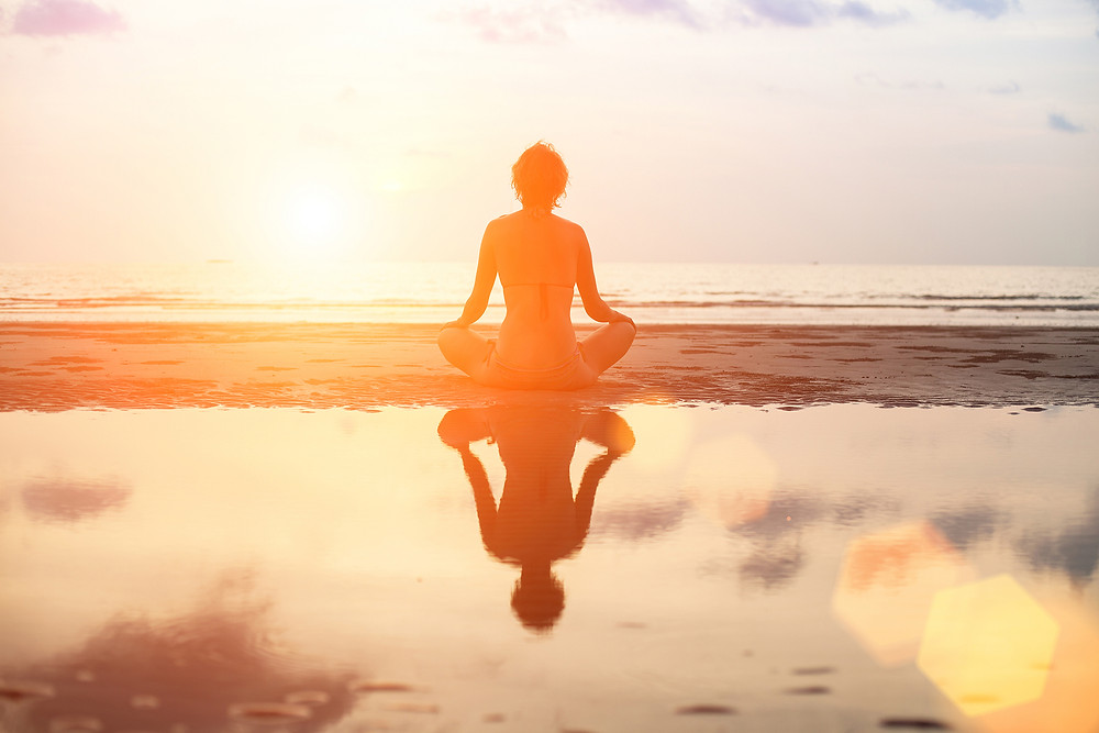 woman meditating on the beach in front of a sunset