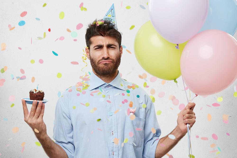Disgruntled Man Holding Balloons