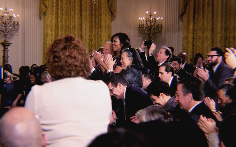 Michelle Obama and a bunch of other political-adjacent humans giving a standing ovation