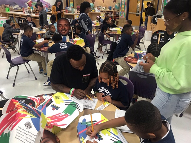 Brandon Carr helping students