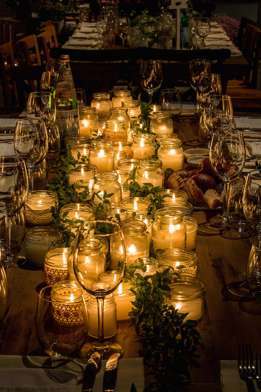 Mason Jar candles wrapped in lace and greenery for a rustic Seder table design