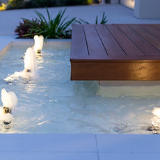 "Up-lit fountains welcome visitors to this ""floating"" portico deck."