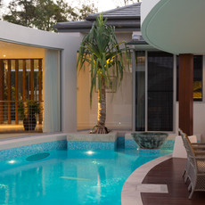This stunning lagoon pool incorporates stone planters and timber entertaining deck.